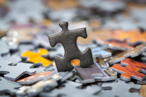 Black jigsaw puzzle piece on heap of color puzzle pieces. Shallow depth of field